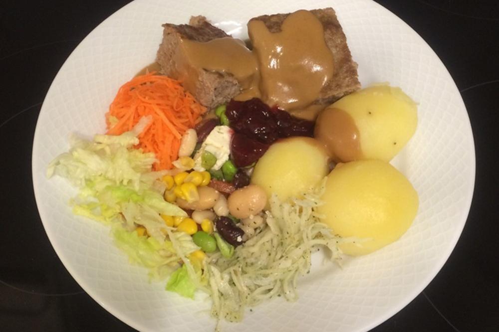 En tallrik med potatis, kött och grönsaker.