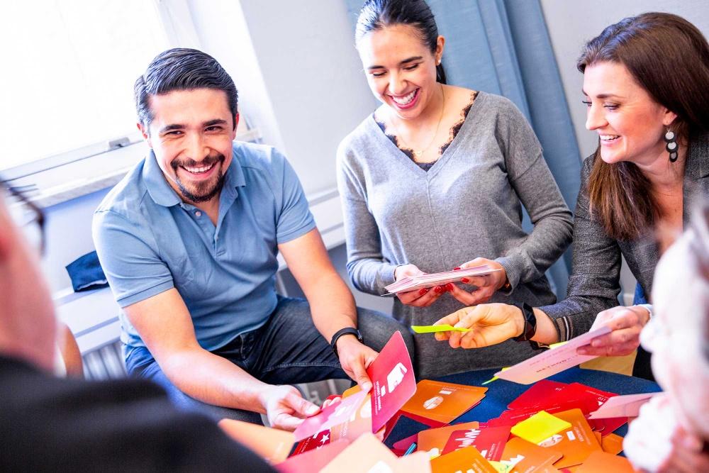 Tre leende personer sitter samlade kring ett bord fyllt av färgglada kort.