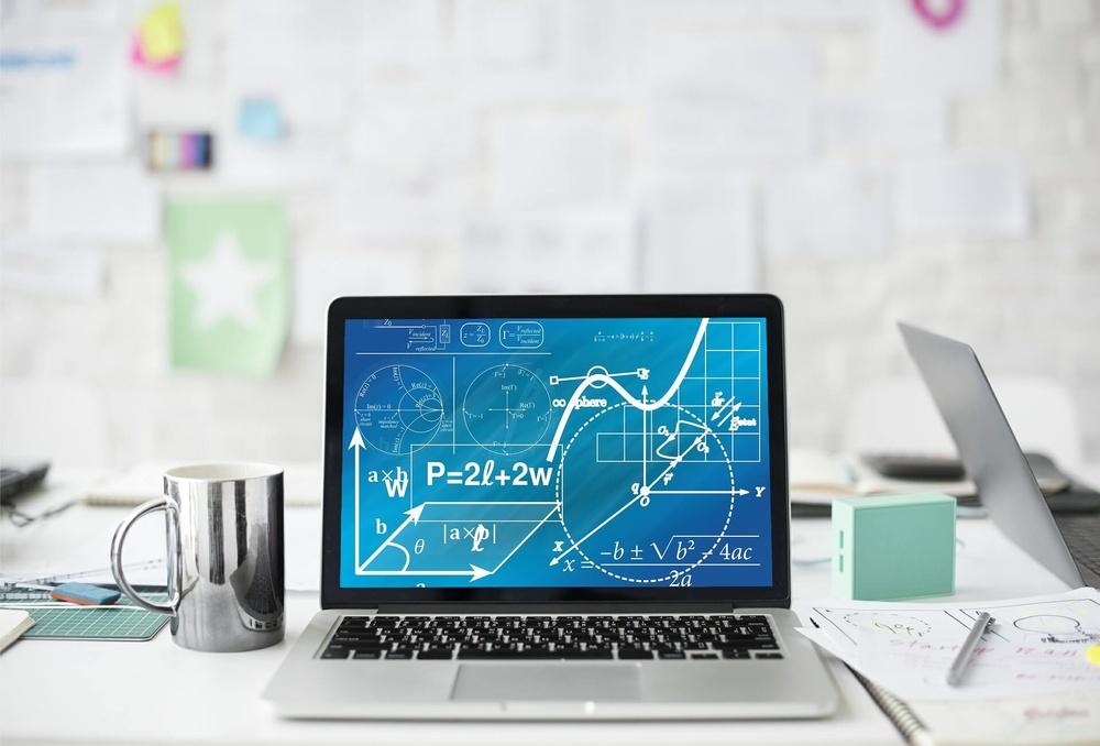 Dator med matematiska formler på bord med kaffekopp