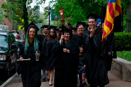A Photo taken by Rory Hamovit, MFA 20 of the 2019 School of Art Commencement Procession. Leading the 2019 degree candidates down York Street, the faculty marshall, Lisa Kereszi, holds the school's mace, while student marshalls hold the school's flag.