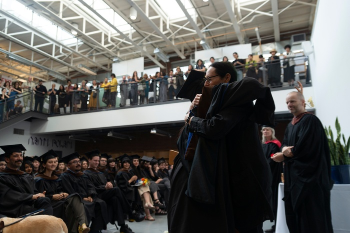 This is a still photo from the 2019 School of Art Commencement Ceremony, in which Director of Graduate Studies in Graphic Design Sheila Levrant de Bretteville hugs a graduating student as she hands him his diploma.