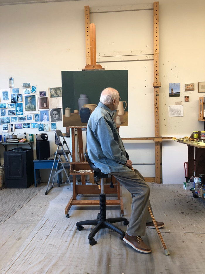 A still image of painter and professor William Bailey sitting in his studio in front of a work-in-progress on an easel.