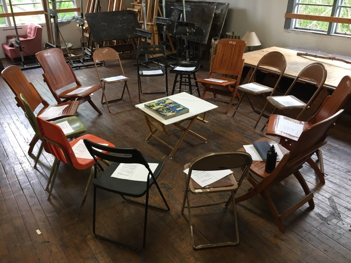 A photograph take at the Yale Norfolk Summer School of Art of a drawing studio containing a circle of chairs around a low table on which a artwork is laid out.