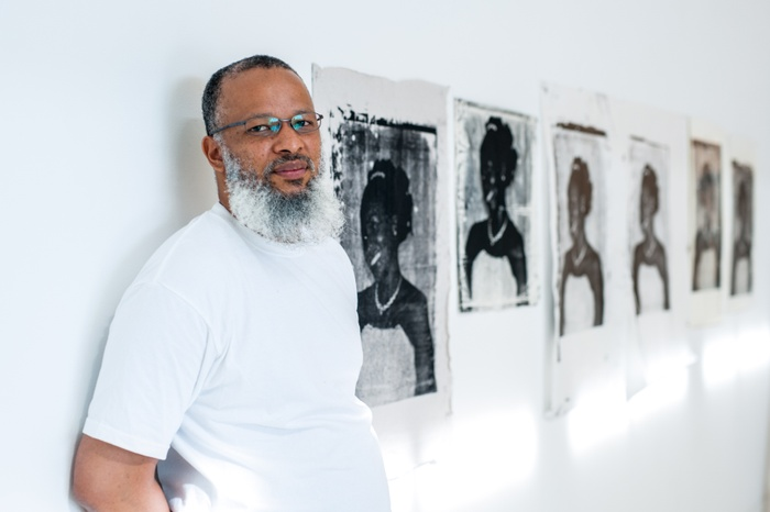 This is a still image of newly appointed Associate Professor in Painting/Printmaking Meleko Mokgosi against a white gallery wall. Behind him are a series of black and white portraits of a woman in a white dress.