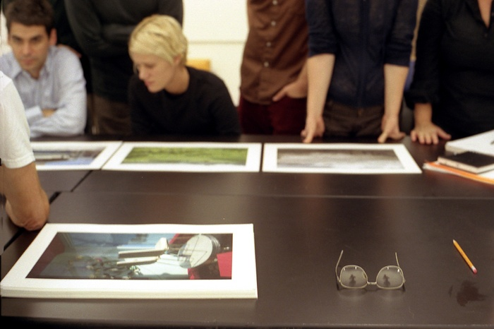 Students examine photographs on a black table.