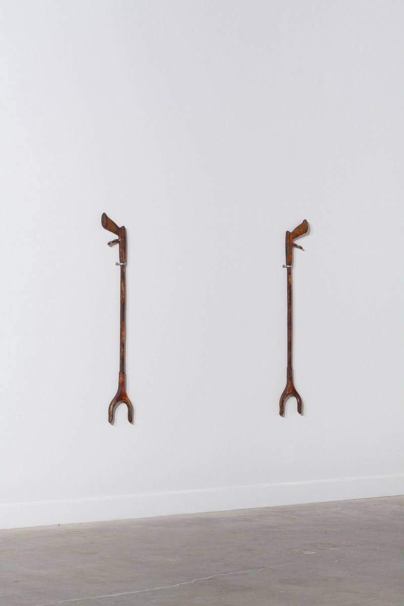 Hanging on a white wall are two large grabbers, similar to ones that Emily uses. The grabbers have a rusted hue.