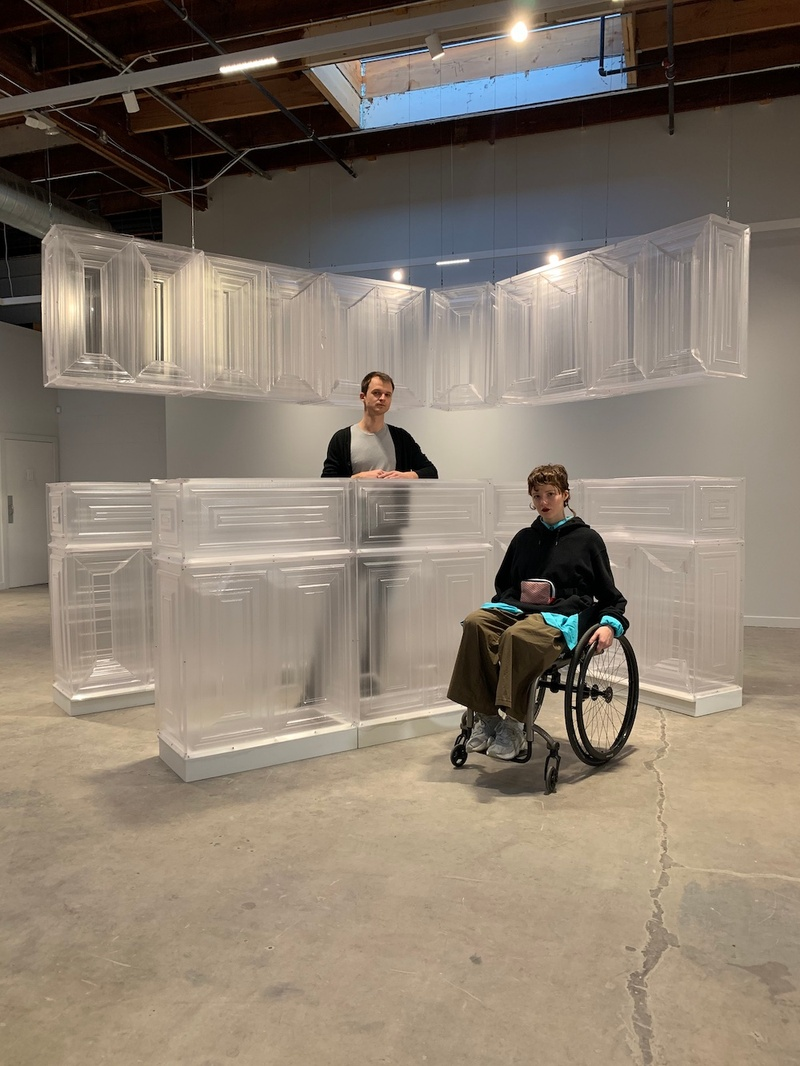 Emily, a white person with red hair, sits in their black wheelchair in front of their sculpture, Untitled (Kitchen). The sculpture consists of large and inaccessible kitchen cabinets, fabricated out of clear plastic. Standing behind one of the cabinets is Tomasz Jan Groza, a white person with dark hair.