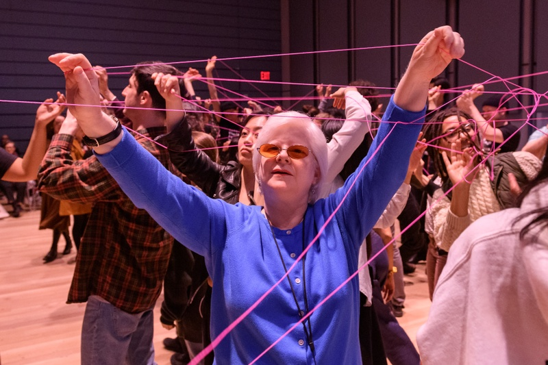 About 100 people stretching their arms while holding pink strings, creating a web of connections. Inside of a large theater.