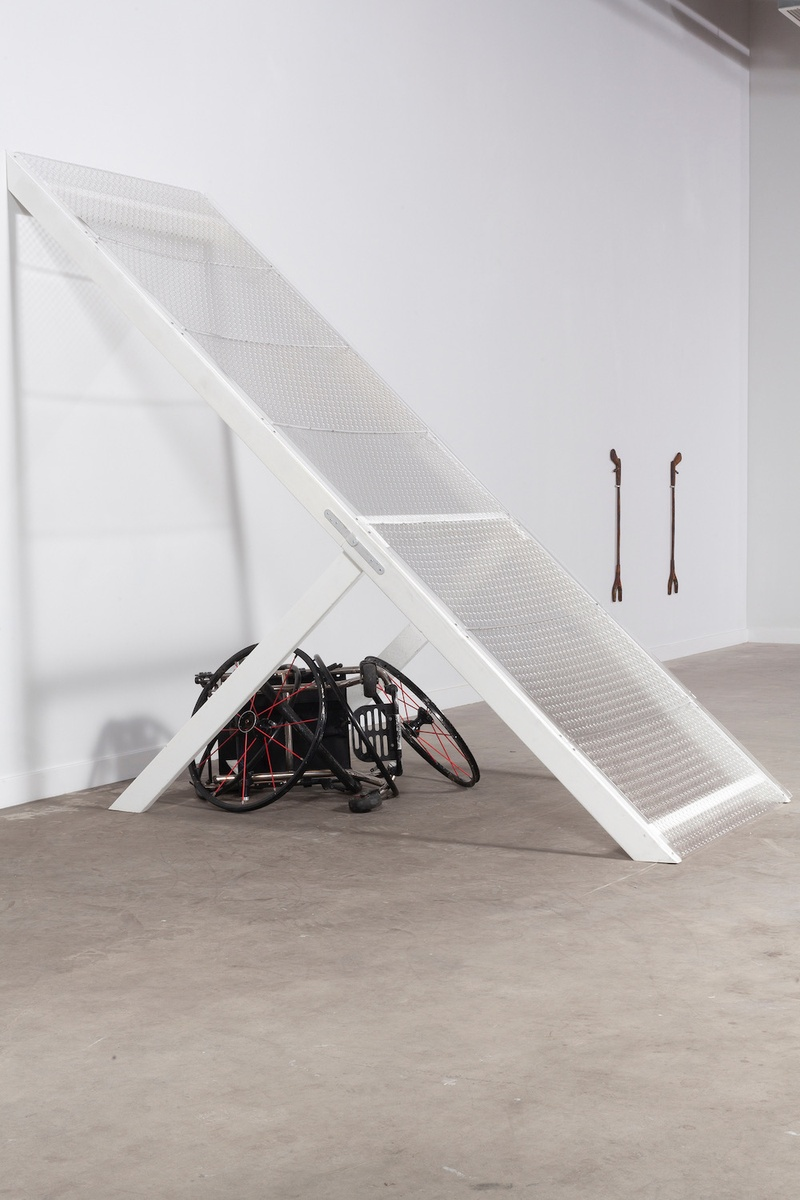 A larger than life ramp is positioned at a steep angle attaching the white wall of the gallery space to the grey floor. Underneath the ramp is a broken black wheelchair. In the distance hanging on the wall is an artwork titled *Grabbers*, consisting of two grabbers similar to the ones Emily uses.