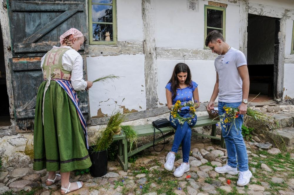 Besökare binder kransar på Gamlegårds innergård, tillsammans med en av Östarps värdar. Foto: Viveca Ohlsson, Kulturen
