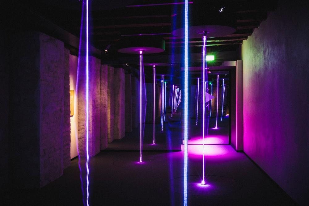 Mörkt rum med lilatonad belysning och lysande strängar från golv till tak.