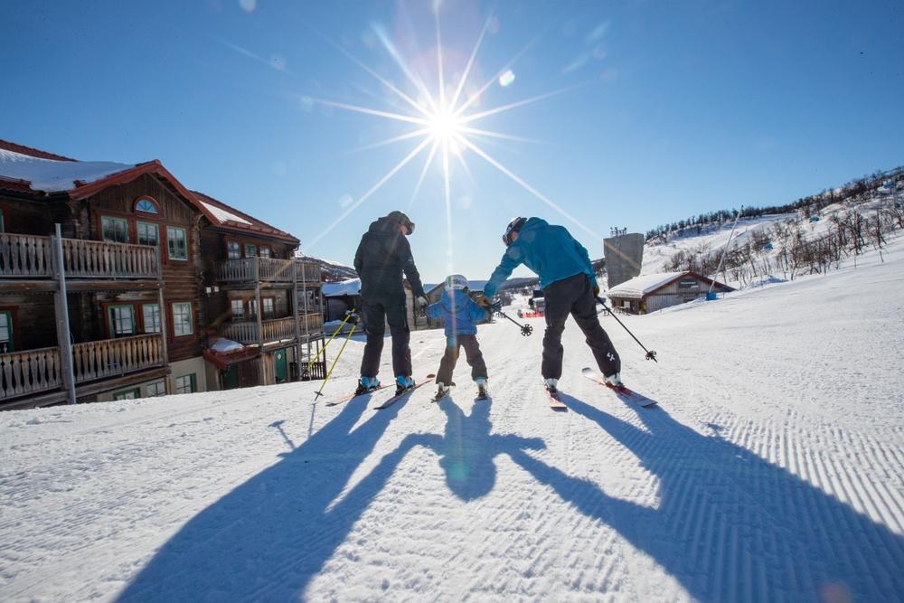 Två vuxna och ett barn som åker slalomskidor