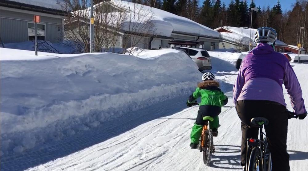 Barn och förälder vintercyklar tillsammans