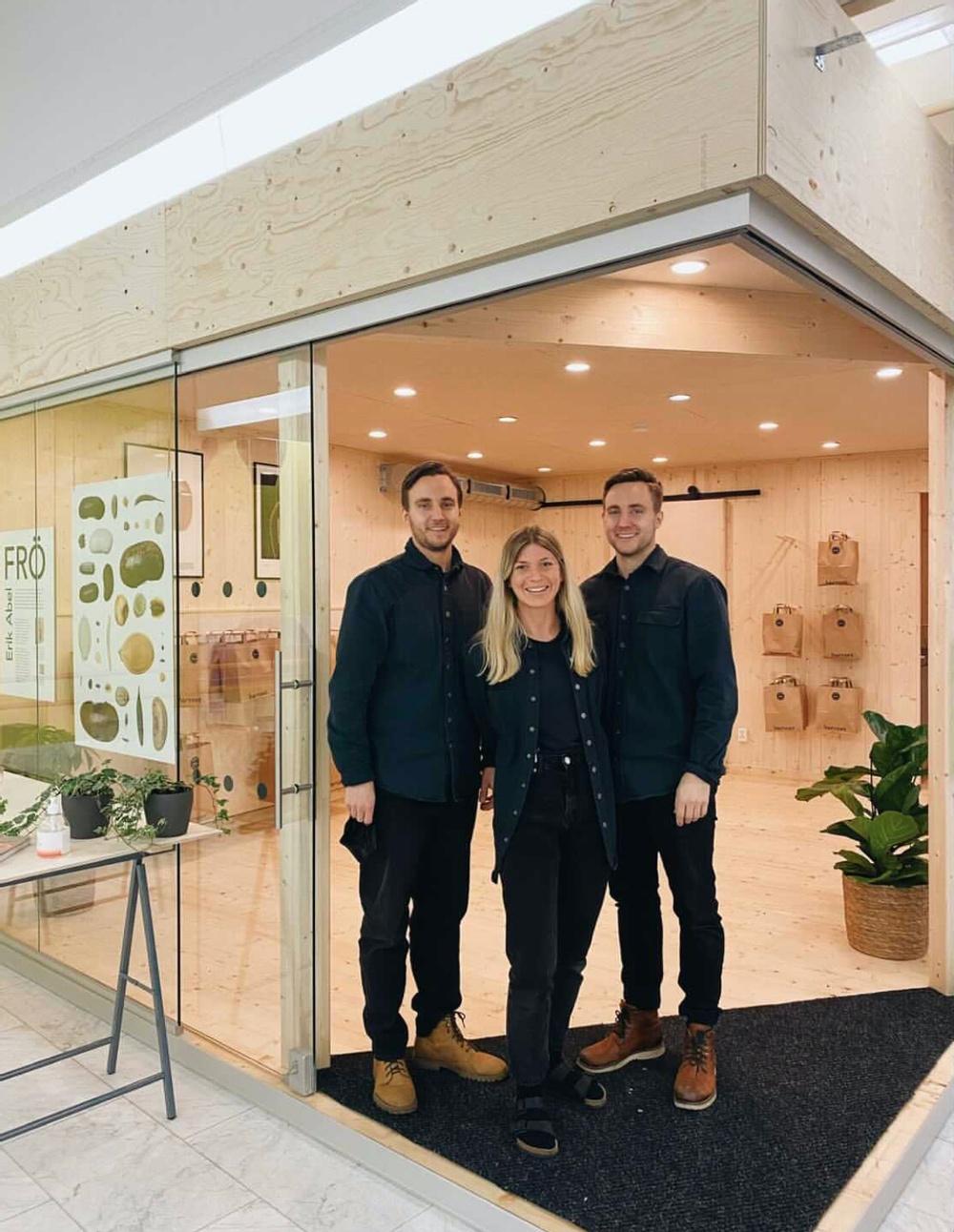 Tre personer i en byggnad av KL-trä.