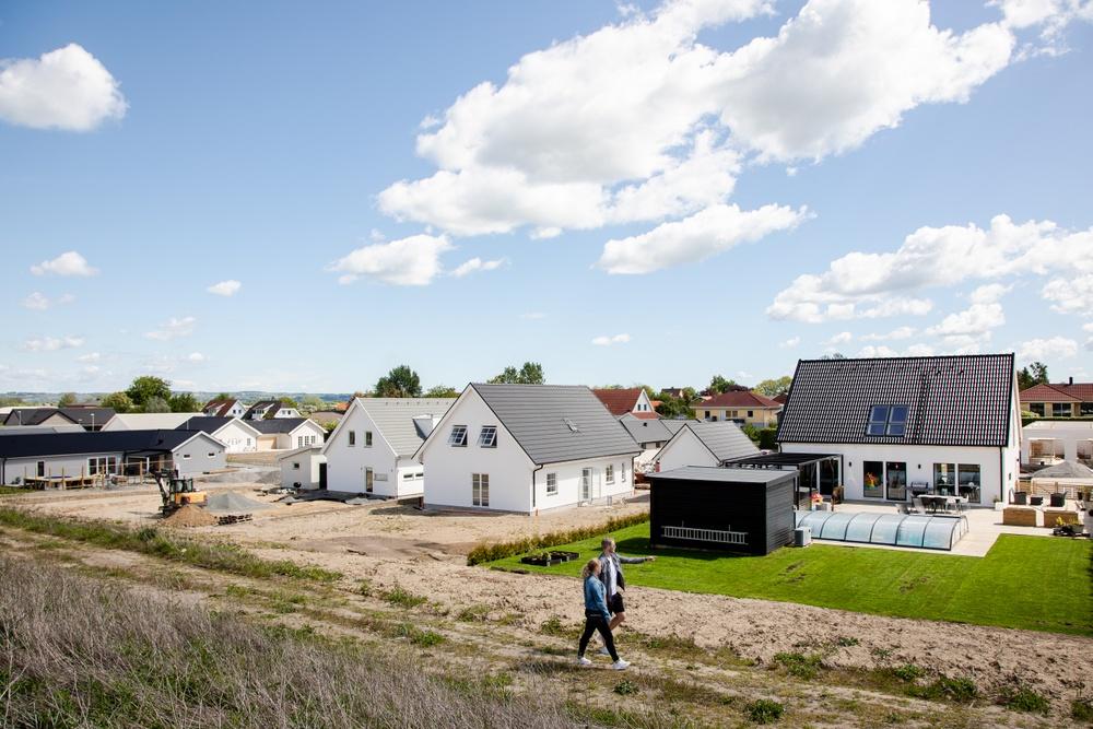 Nytt bostadsområde byggs upp. Vita hus, oberedd mark. Ett ungt par går i förgrunden.