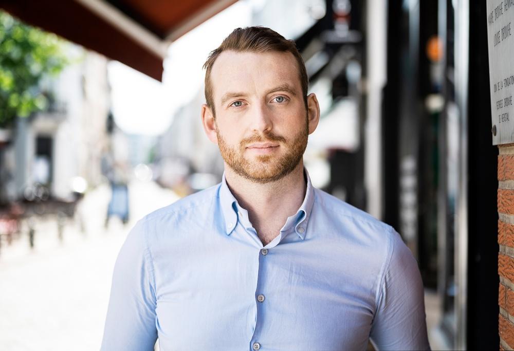 Jakop Dalunde står på en trottoar i bå skjorta, ser allvarlig ut