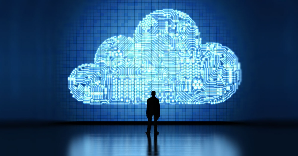 Man stands dwarfed by a technological cloud.