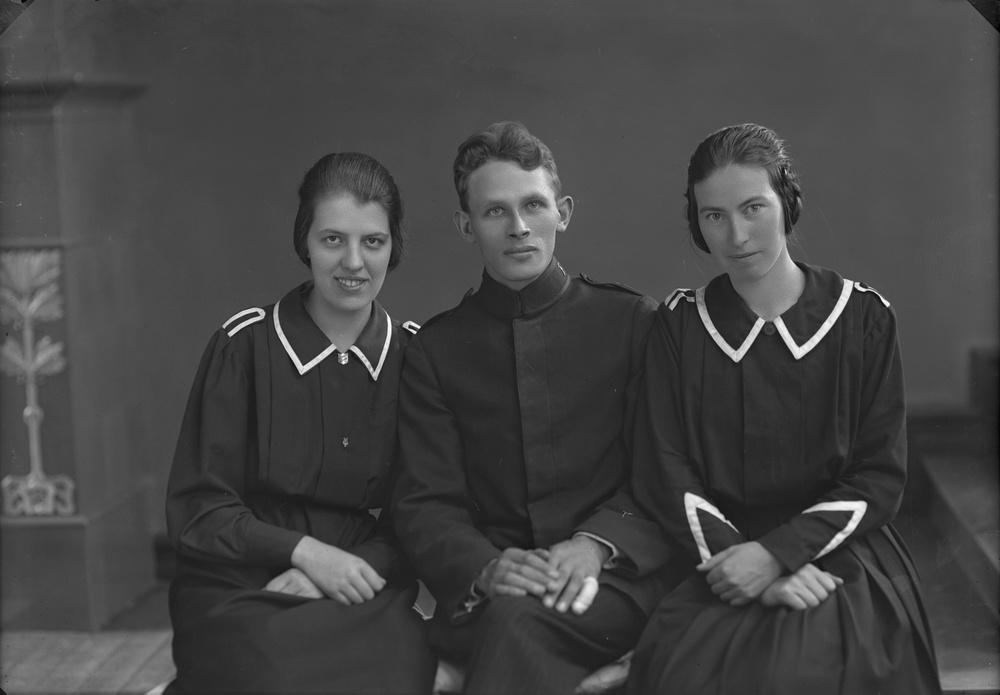 Porträtt av två kvinnor klädda i klänningsuniformer och man klädd i militär uniform. Foto: Ida Ekelund, ur Kulturens samlingar.