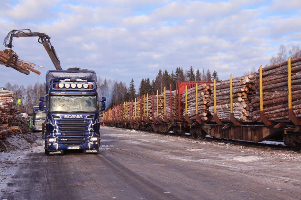 Virkesbil som lastar av virke samt tåg med virke