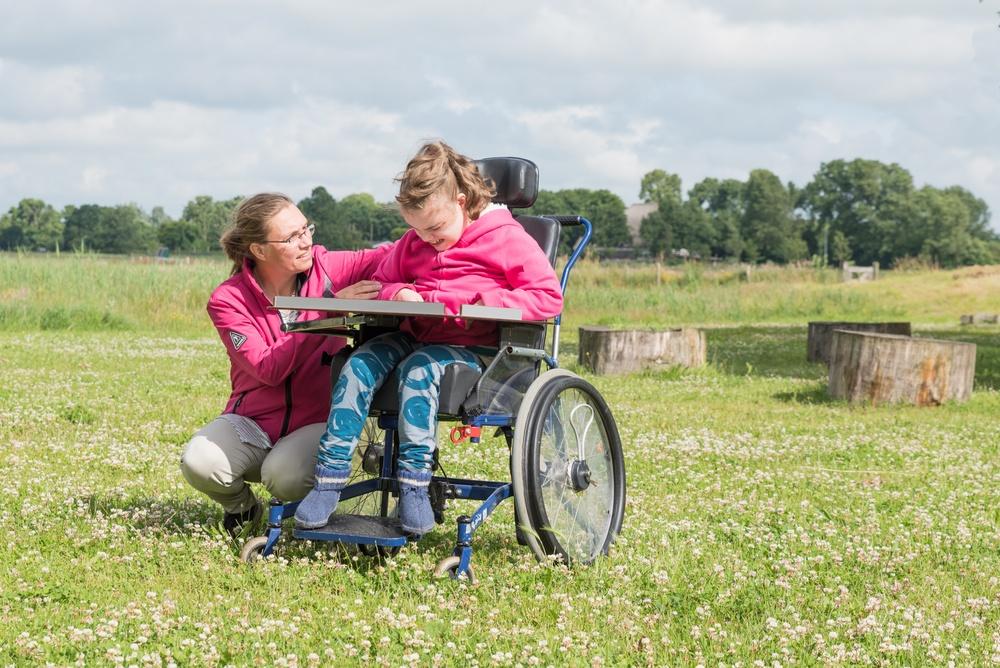 Personlig assistent sitter ned bredvid ung flicka i rullstol. Flickan använder bilder som stöd för kommunikation. Båda befinner sig utomhus.