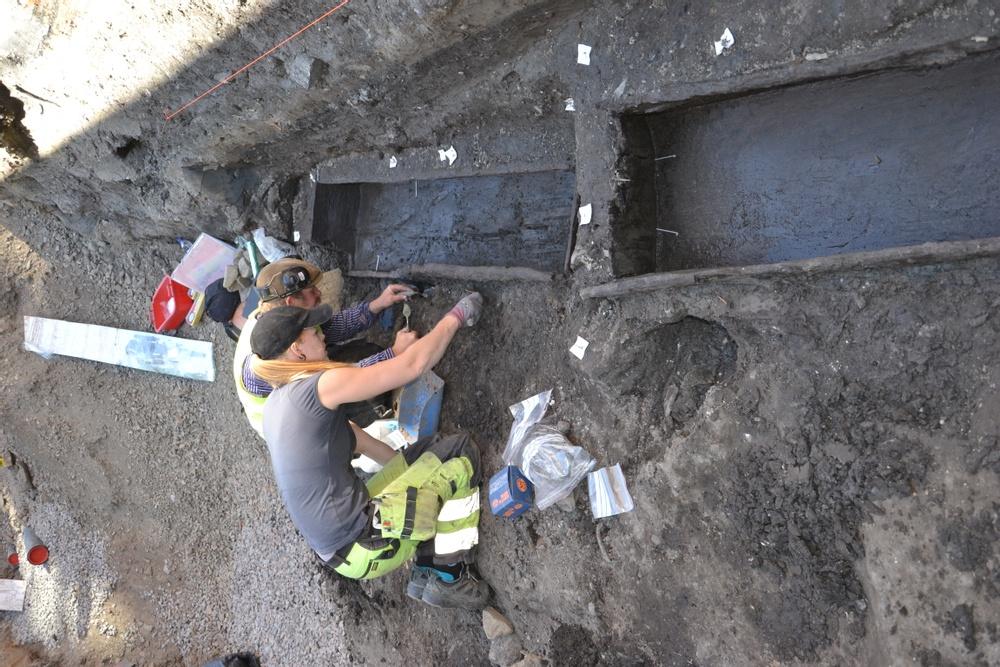 Linnea Lidh och Olof Andersson rensar fram två hela träkistor som påträffades i Västra Mårtensgatan i juni 2020. Foto: Kulturens arkeologer.