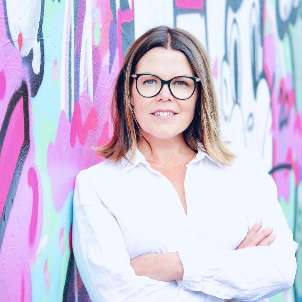 Anna Rosengren VD på Almi GävleDala står vid en grafittivägg.